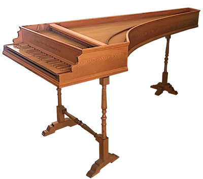 Image of a brown natural wood harpsichord. The cover is removed and the keys are visible. The legs of the stand are turned with ovoid shapes and long blocks.