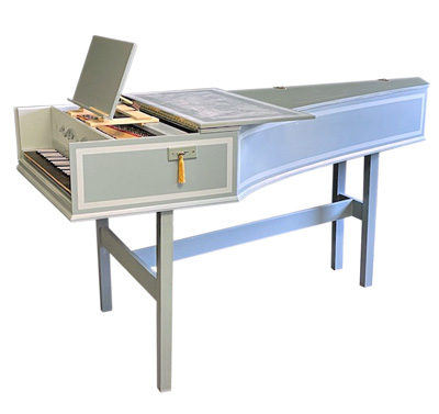 Image of a single manual harpsichord. It is a pale green color with white accents and a yellow tassel.