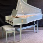 Image of a single manual harpsichord with open lid and bench. It is a pale green color with white accents and a yellow tassel.