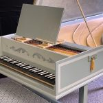Image of a single manual harpsichord. It is a pale green color with white accents and a yellow tassel showing the keyboard.