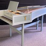 Image of a single manual harpsichord with partly open lid. It is a pale green color with white accents and a yellow tassel.