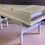 Image of a single manual harpsichord. It is a pale green color with white accents.
