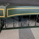 Image of a green harpsichord with closed lid. The case and lid are accented with gold boxes.
