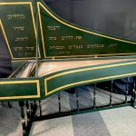 Image of a green harpsichord with open lid. The case and lid are accented with gold boxes and there is hebrew text inside the lid.