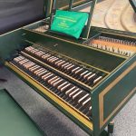 Image of a green harpsichord with open lid and music stand. The case and lid are accented with gold boxes