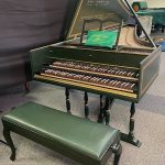 Image of a green harpsichord with open lid and music stand behind a green bench. The case and lid are accented with gold boxes.