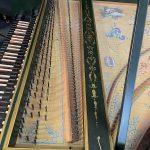 Detail of harpsichord tuning pegs, keyboard and soundboard painting.