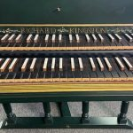 Image of a harpsichord keyboard with black keys and white accidentals.